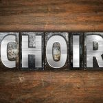 "The word ""Choir"" written in vintage metal letterpress type on an aged wooden background."